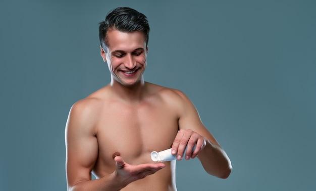 Bel giovane isolato. ritratto di uomo muscoloso senza camicia è in piedi su sfondo grigio e usa la crema per il viso. concetto di cura degli uomini.