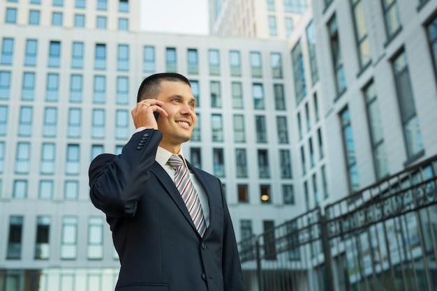 Bel giovane uomo in giacca con il telefono in mano sulla costruzione di sfondo