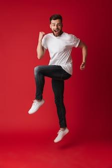 Bel giovane uomo che salta mostrando il gesto del vincitore.