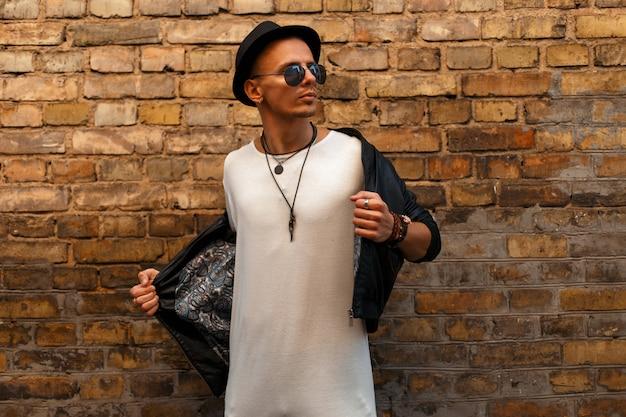 Bel giovane in una giacca di pelle nera con un cappello e una maglietta bianca che indossa occhiali da sole vicino al muro di mattoni