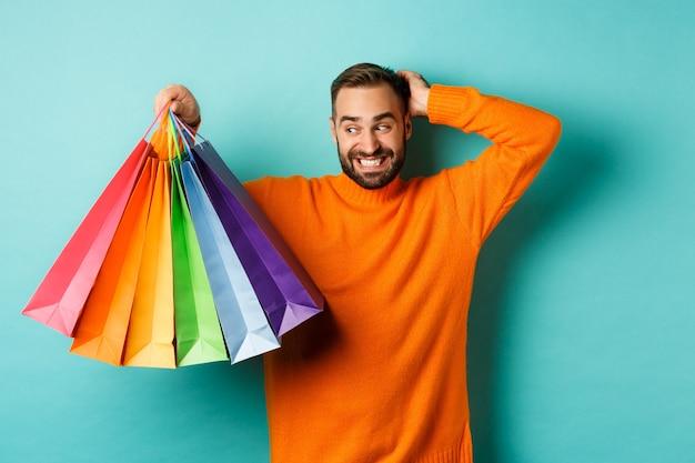 Bel giovane che sembra goffo e graffiare la testa, fissando le borse della spesa con doni, in piedi su sfondo turchese.
