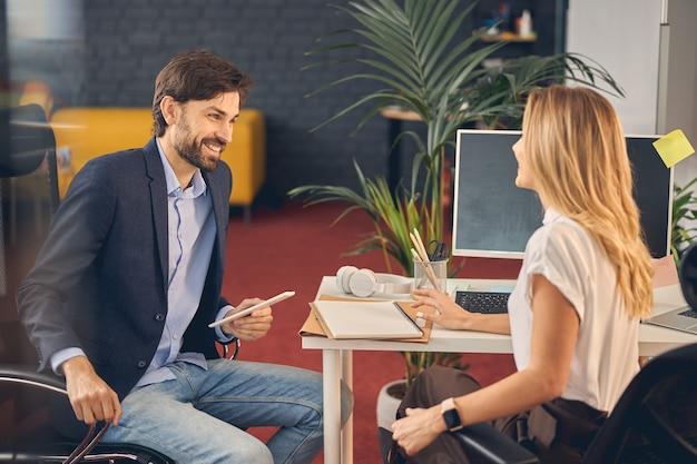 Bel giovane che guarda una signora affascinante e sorride mentre è seduta al tavolo con computer e documenti