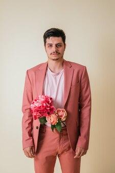 Bel giovane che osserva con i fiori dentro i pantaloni, indossa un abito rosa