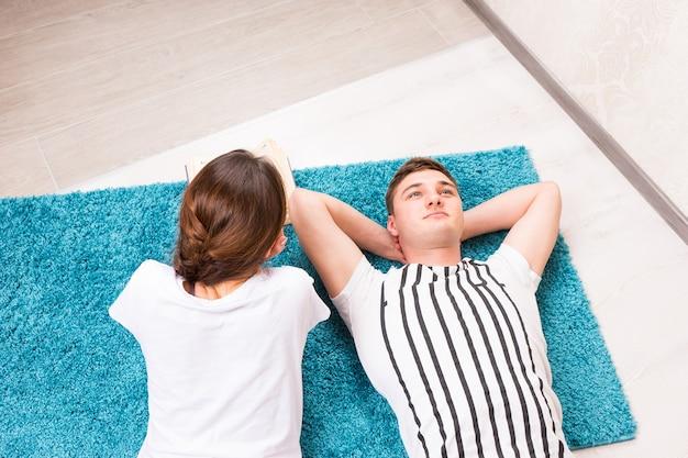 Bel giovane sdraiato su un tappeto vicino a sua moglie nel loro soggiorno in un'atmosfera rilassata