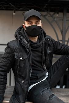 Bel giovane modello con berretto nero e maschera medica protettiva in giacca nera e felpa con cappuccio si siede per strada