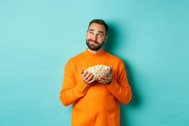 Bel giovane in maglione arancione, guardando pensieroso nell'angolo in alto a sinistra, tenendo popcorn, film di raccolta, sfondo blu.