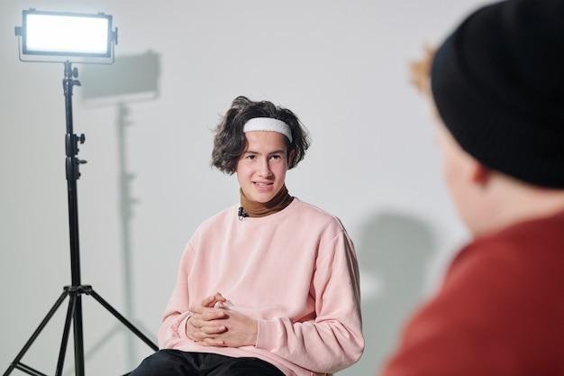 Bel giovane in pullover rosa cipria e fascia bianca che comunica con il vlogger davanti a lui