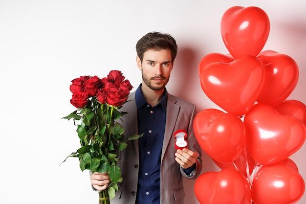 Bel giovane prepararsi a fare una proposta, tenendo l'anello di fidanzamento con bouquet di rose rosse, facendo sorpresa il giorno di san valentino, in piedi vicino a palloncini cuore, sfondo bianco.