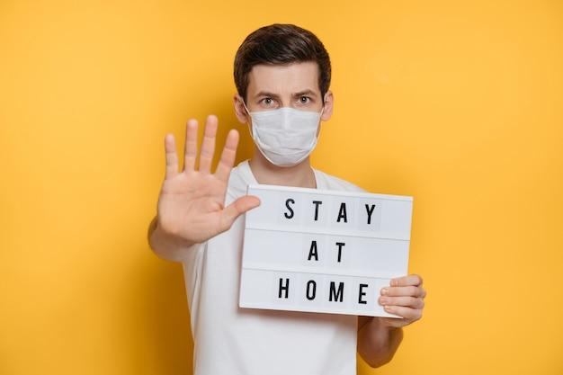 Bel giovane con maschera protettiva tiene il cartello stay at home e mostra il gesto di arresto per prevenire l'infezione da coronavirus.