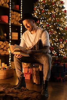 Bel giovane uomo lettura libro vicino all'albero di natale a casa.