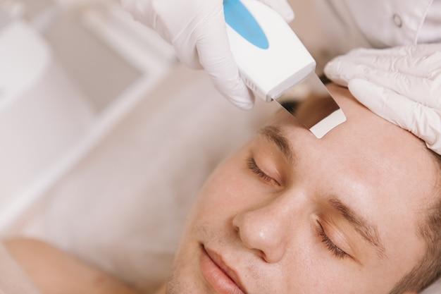 Bel giovane uomo che riceve un trattamento di cura della pelle al salone di bellezza