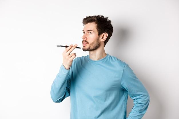 Bel giovane che registra il messaggio vocale sullo smartphone, tenendo il telefono vicino alle labbra e parlando. guy utilizzando l'app traduttore sul telefono cellulare, sfondo bianco.
