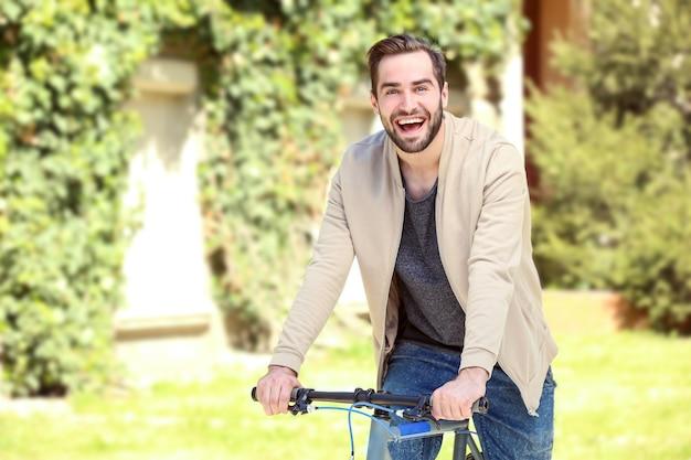 Bel giovane in bicicletta all'aperto in giornata di sole