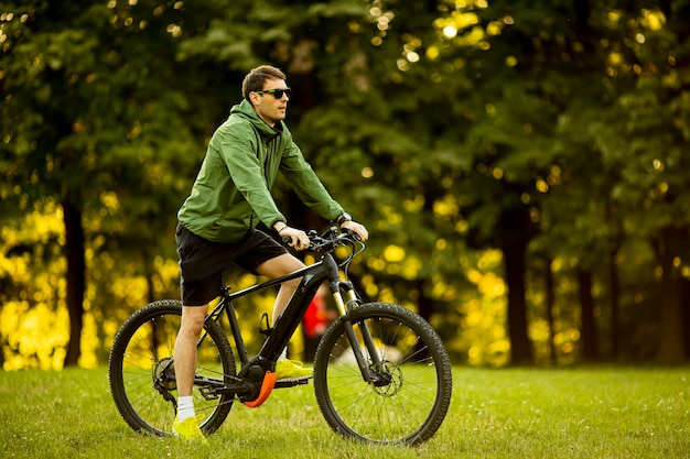 Bel giovane uomo equitazione ebike nel parco