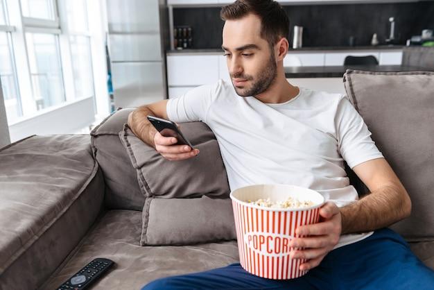 Bel giovane seduto su un divano a casa, mangiando popcorn, guardando la tv, usando il cellulare