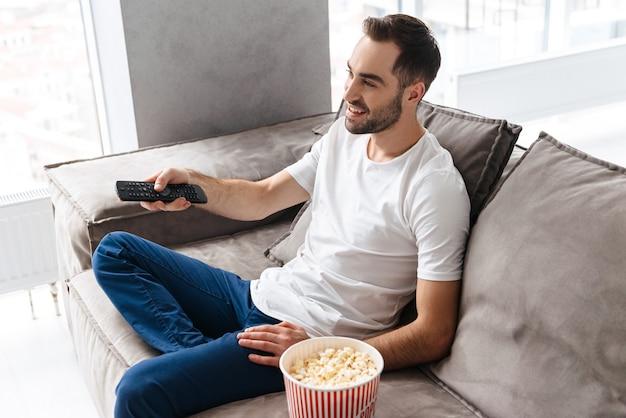 Bel giovane seduto su un divano a casa, mangiando popcorn, guardando la tv