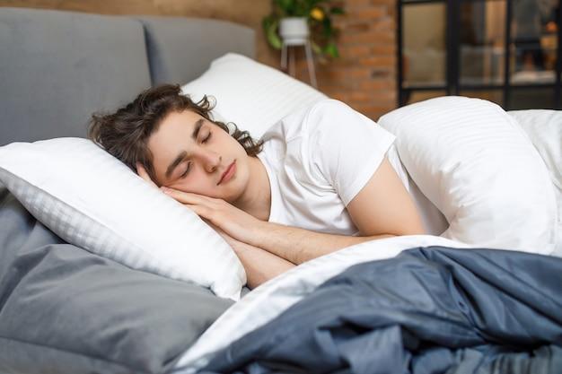 Bel giovane che dorme nel letto