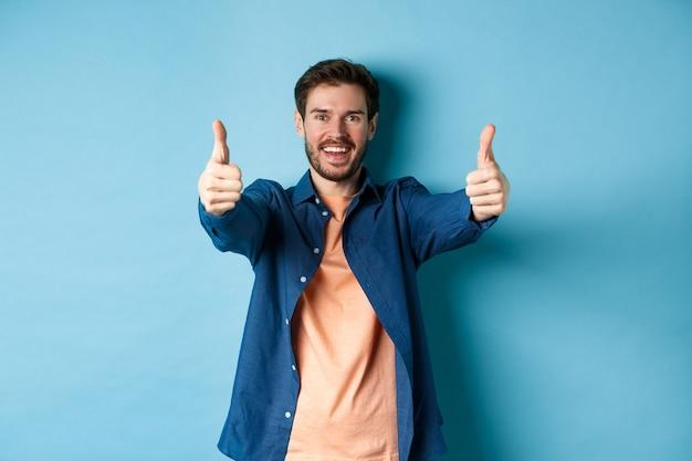 Bel giovane uomo sorridente e mostrando i pollici in su in approvazione, dire di sì con la faccia felice, in piedi su sfondo blu.
