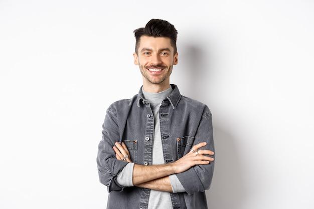 Bel giovane uomo sorridente con le braccia incrociate sul petto, sentendosi pronto, guardando motivato alla telecamera, in piedi su sfondo bianco.