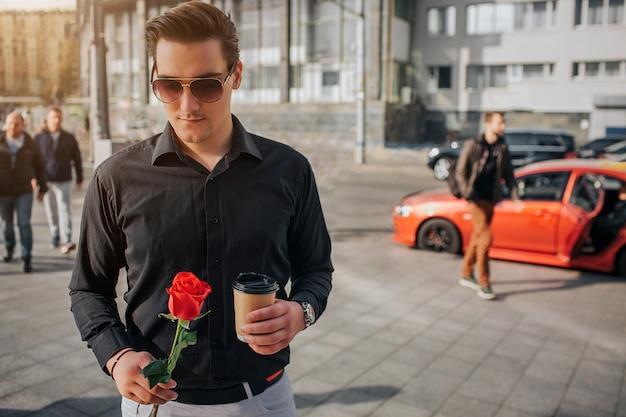 Giovane bello stare fuori. tiene una rosa rossa e una tazza di drink. guy indossa occhiali da sole. ci sono persone e macchine dietro di lui.