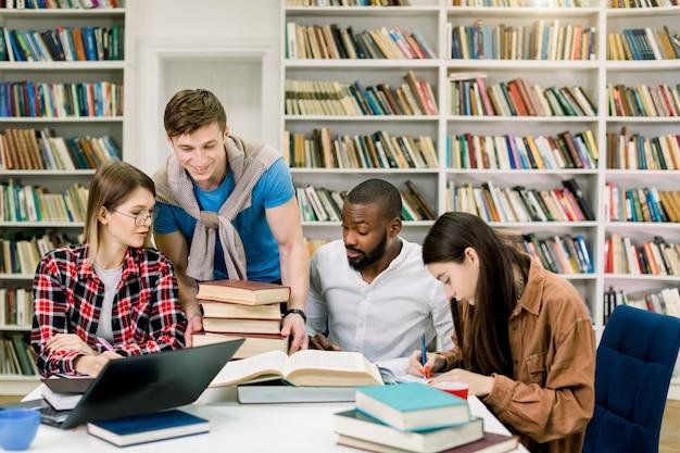Studente bello del giovane che mette molti libri differenti sul tavolo per i suoi multi amici razziali dell'università, sedentesi e studianti nella sala di lettura moderna della biblioteca del campus universitario.