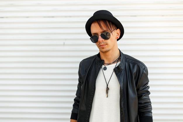 Bel giovane in abiti eleganti con occhiali da sole in posa vicino al muro di metallo bianco