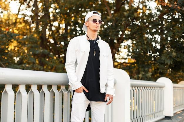 Bel giovane in eleganti occhiali da sole e una giacca bianca con un berretto da baseball nel parco in una giornata autunnale