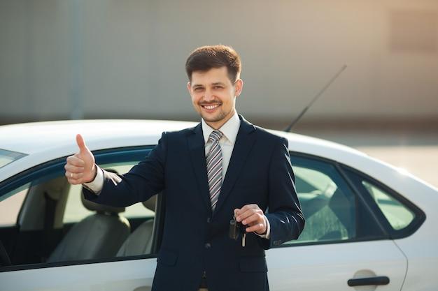 Bel giovane in giacca e cravatta ha comprato una macchina con le chiavi in mano