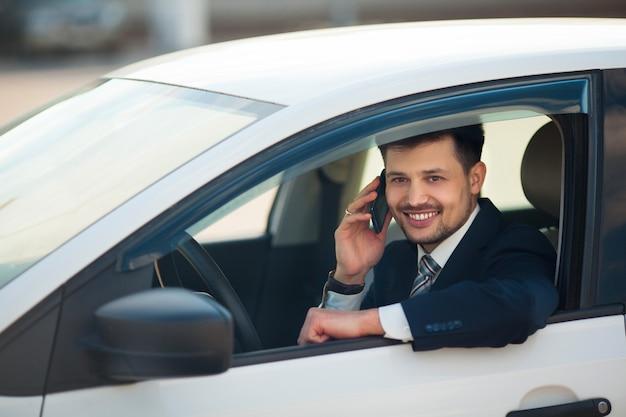 Bel giovane uomo in un vestito parlando al telefono seduto in macchina