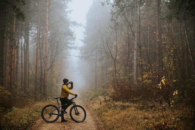 Bel giovane che prende un freno durante la bicicletta attraverso la foresta di autunno