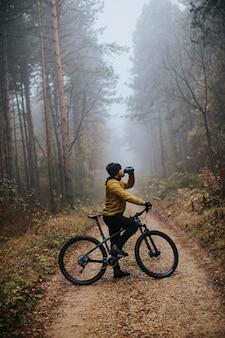 Bel giovane prendendo un freno durante la bicicletta attraverso la foresta di autunno