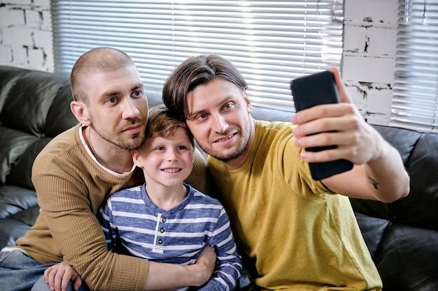 Bel giovane che si fa selfie con suo figlio e suo marito quando è seduto sul divano di casa