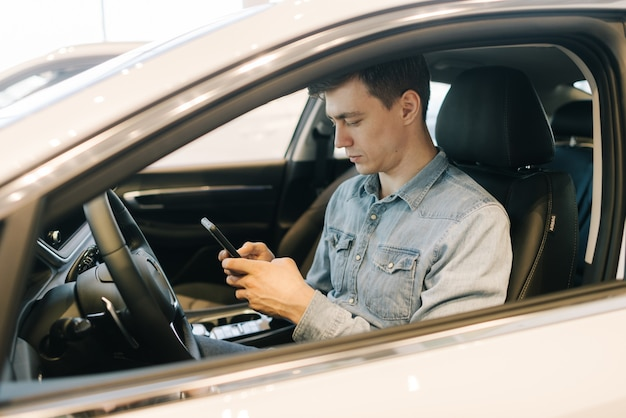 Il giovane bello che usa il telefono cellulare si siede al volante dell'auto