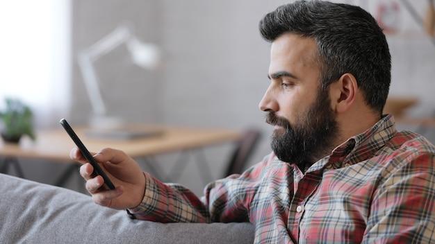 Bel giovane che utilizza smartphone seduto a casa.