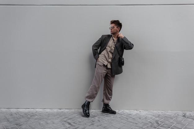 Bel giovane che indossa abiti alla moda guarda con blazer, camicia e stivali in posa vicino a un muro grigio per strada. stile e moda maschile casual