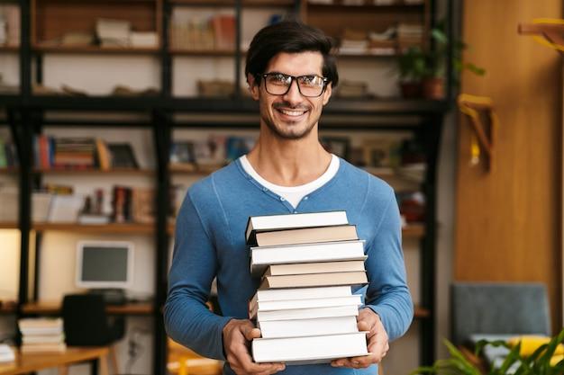 Bel giovane uomo con gli occhiali in piedi presso la biblioteca, tenendo in mano una pila di libri