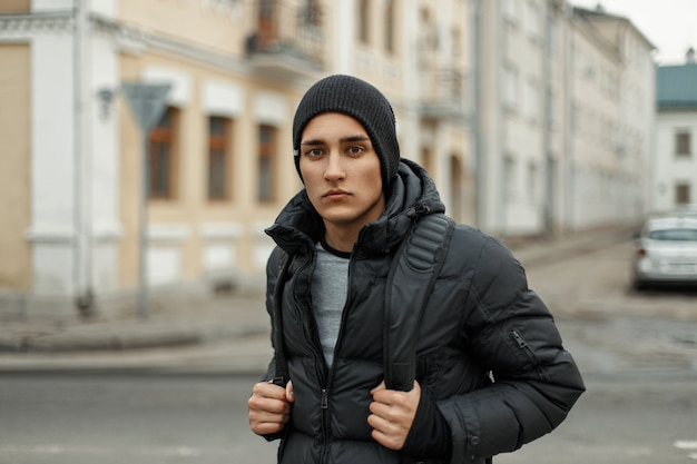 Bel giovane in giacca invernale e cappello nero lavorato a maglia sullo sfondo della città