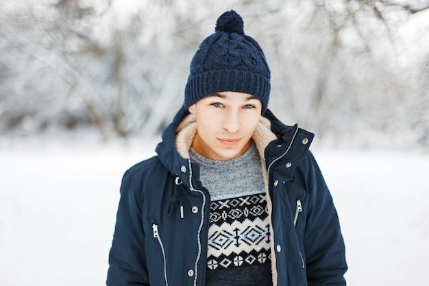 Bel giovane in giacca invernale, maglione lavorato a maglia con un motivo e un cappello lavorato a maglia