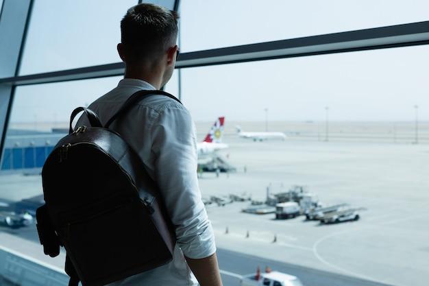 Bel giovane con uno zaino in aeroporto