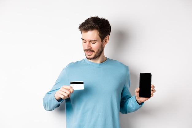 Bel giovane con la barba, mostrando lo schermo vuoto dello smartphone e guardando la carta di credito in plastica, in piedi su sfondo bianco.