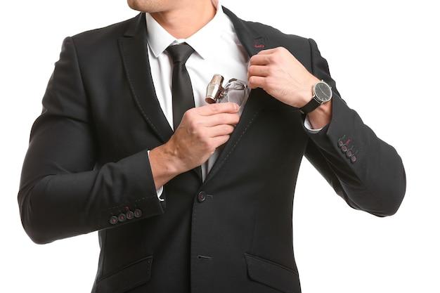 Bel giovane con bottiglia di profumo su bianco, primo piano