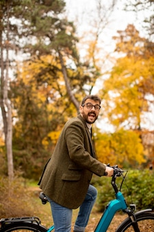 Bel giovane con bicicletta elettrica nel parco autunnale