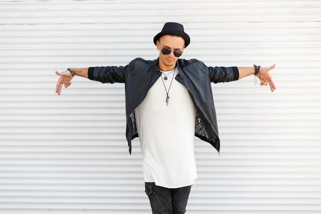 Bel giovane con un cappello alla moda indossa occhiali da sole in abiti alla moda e alla moda vicino al muro di metallo bianco