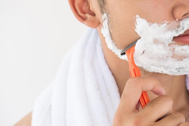 Bel giovane uomo con schiuma sul suo volto è barba da barba.