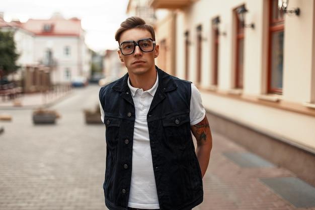 Bel giovane con occhiali e jeans vestiti in città