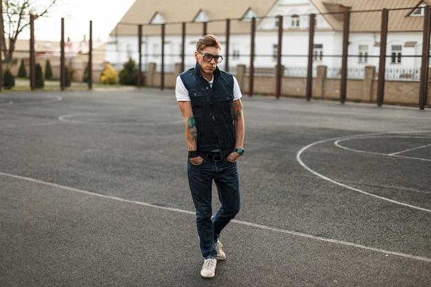 Bel giovane con gli occhiali in stile jeans vintage camminando lungo la strada