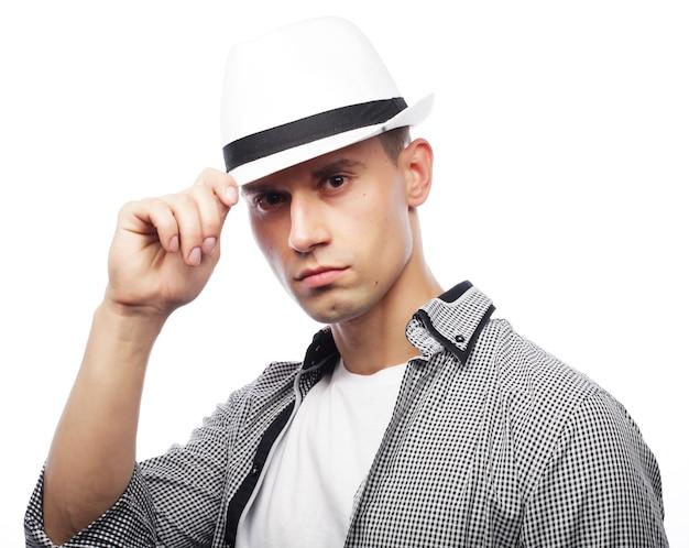 Bel giovane con cappello isolato su sfondo bianco