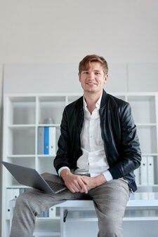 Bel giovane con un bel sorriso seduto sul tavolo in ufficio lavorando sul suo computer portatile.