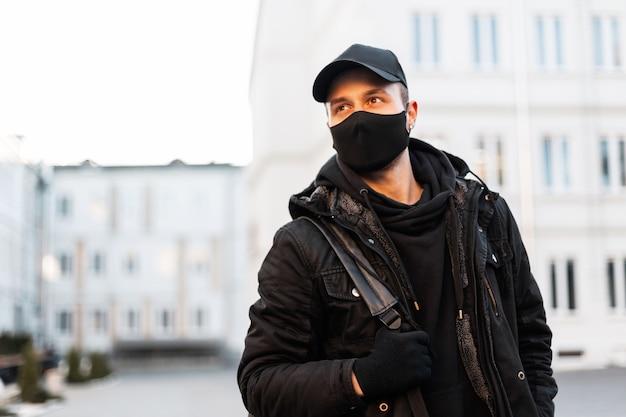Bel giovane con una maschera medica in abiti neri alla moda con una giacca, una felpa con cappuccio e un berretto con uno zaino cammina per la città.