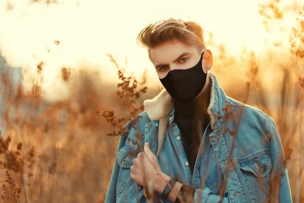 Bel giovane con maschera protettiva medica in vestiti di jeans alla moda guarda con un maglione guardando la telecamera all'aperto al tramonto